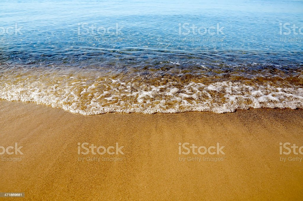 Gold sand and blue water royalty-free stock photo