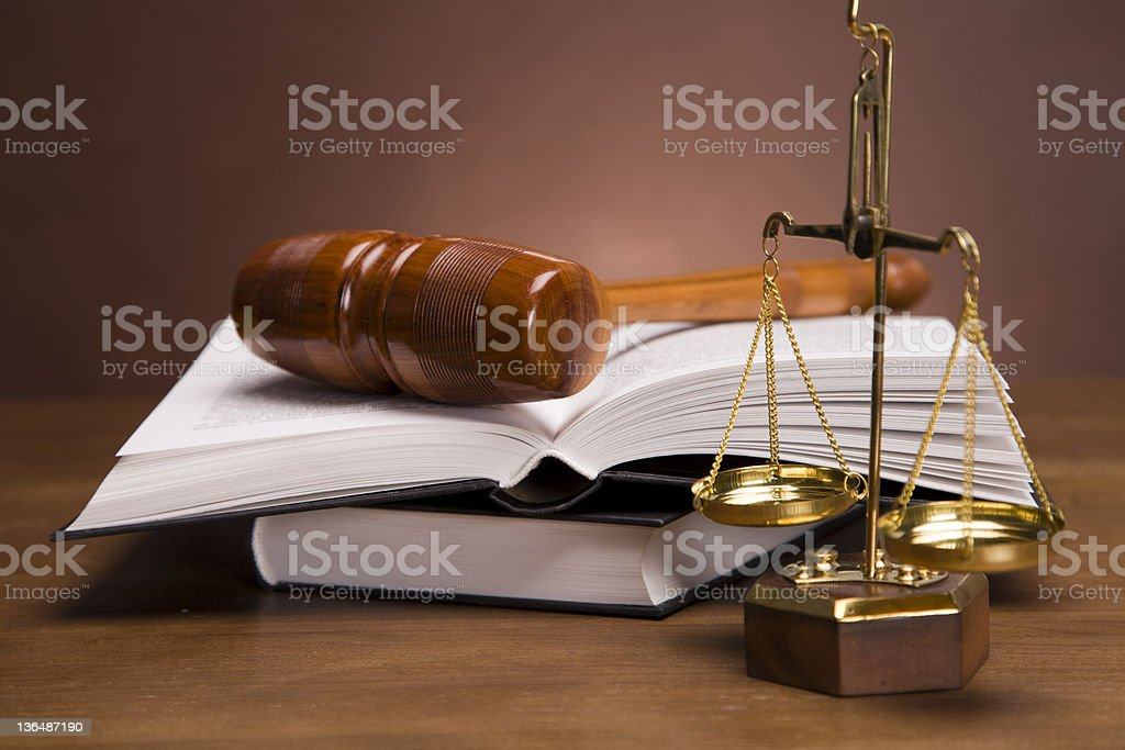 Gold scales, wooden gavel and the legal code in books royalty-free stock photo