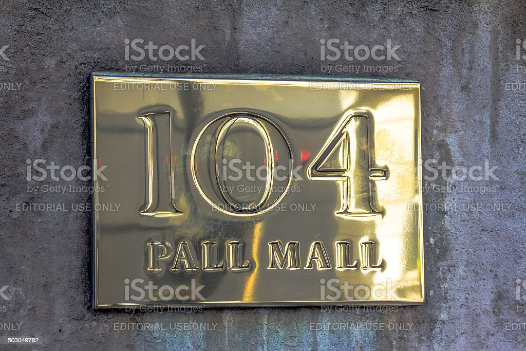 Gold sign PALL MALL 104 on the stone wall stock photo