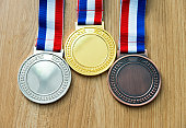 Gold, silver, and bronze medal on wood desk