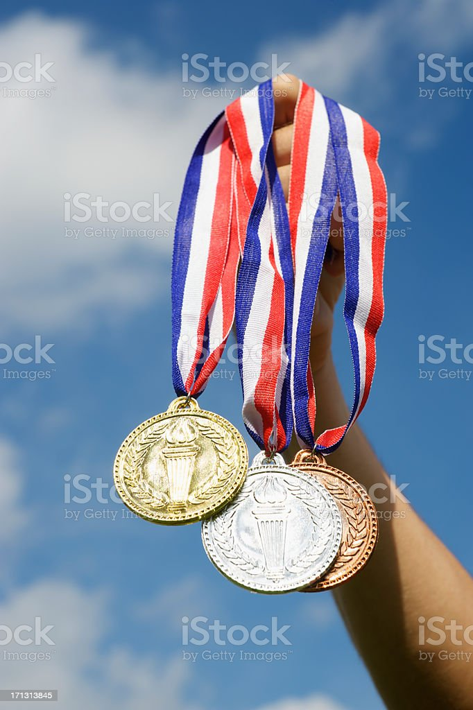 Gold Silver and Bronze Medals Hanging Hand Holding Blue Sky stock photo