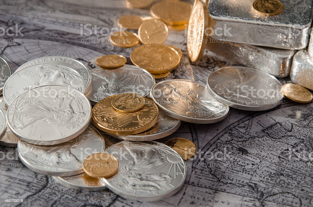 Gold & Silver Coins with Silver Bars on map stock photo
