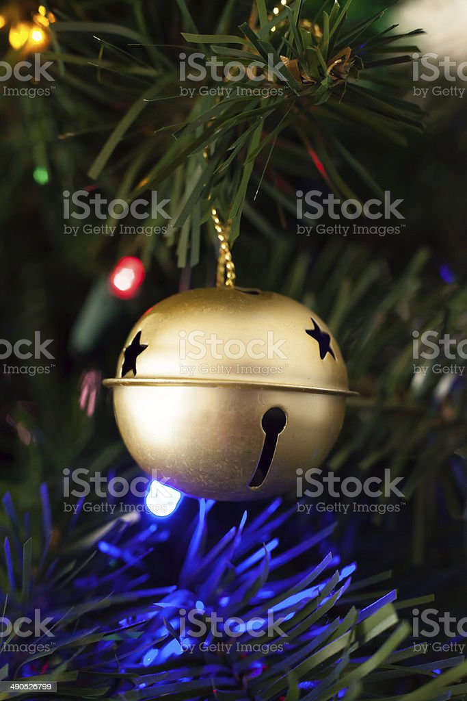 Gold Sleigh Bell Ornament Hung on an Artificial Christmas Tree stock photo