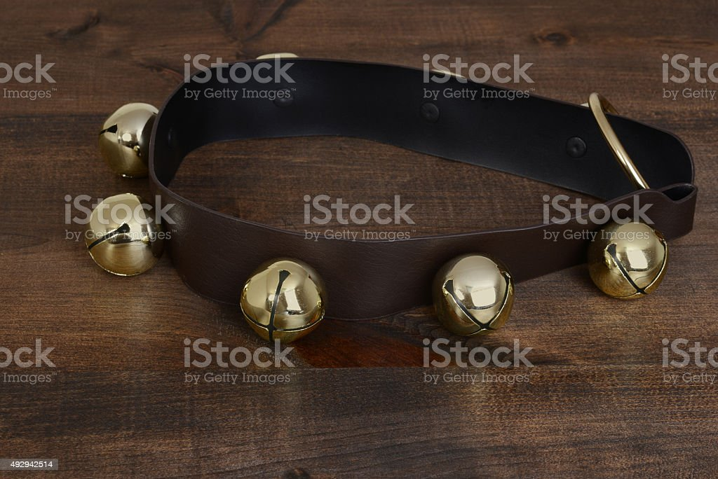 gold sleigh bells on wood stock photo