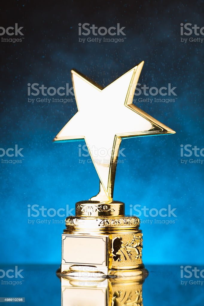 gold star trophy against blue particles background stock photo