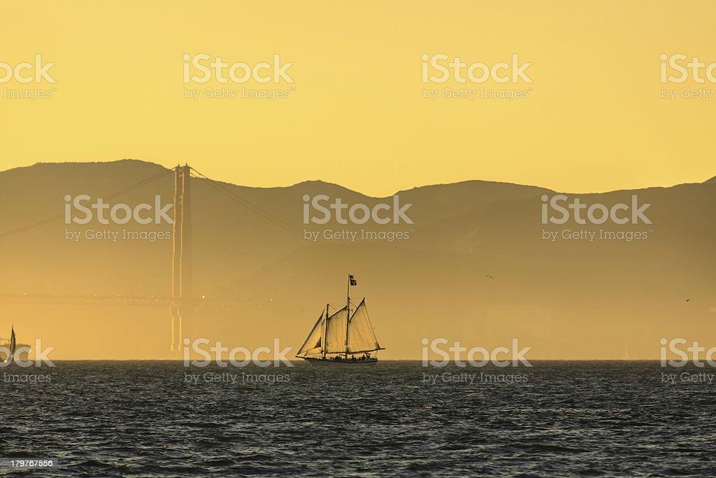 Gold sunrise on Sailboat and Golden Gate Bridge royalty-free stock photo