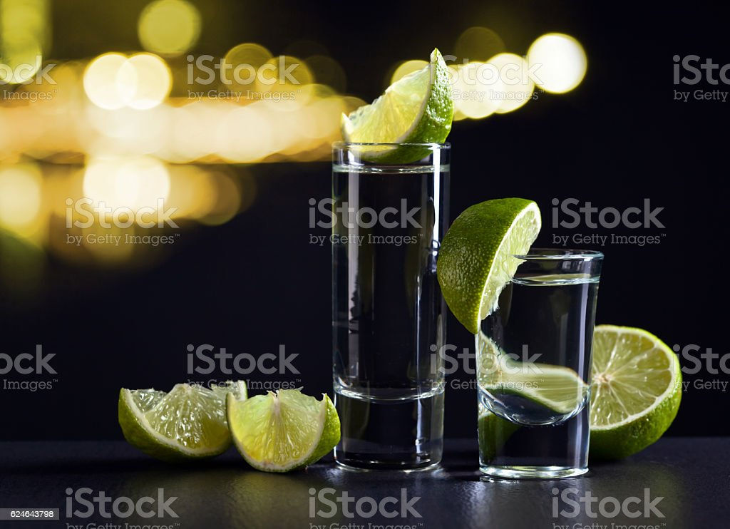 Gold tequila and lime on black table stock photo