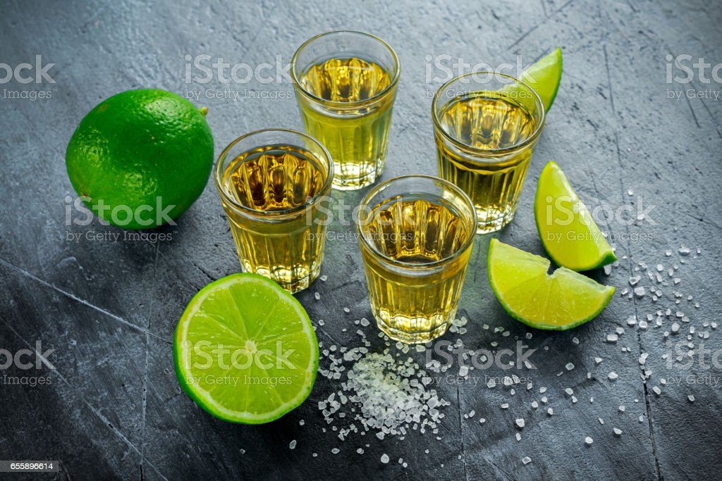 Gold Tequila shots with lime and sea salt stock photo