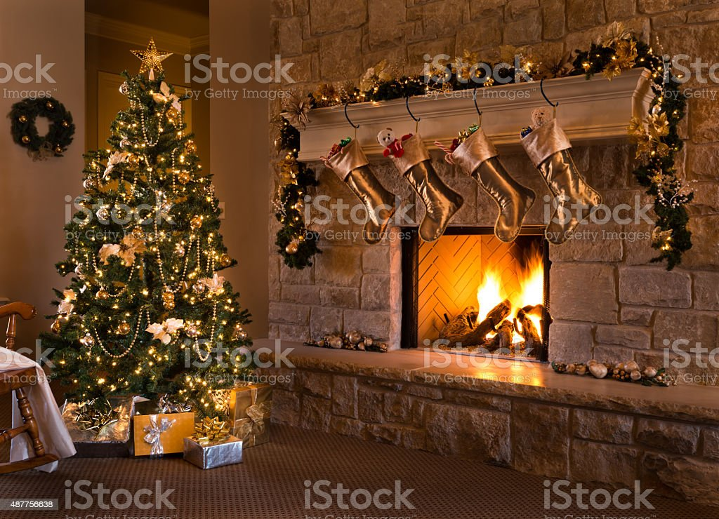 Gold Theme Christmas Eve: tree, fireplace, stockings, gifts, mantel, hearth stock photo