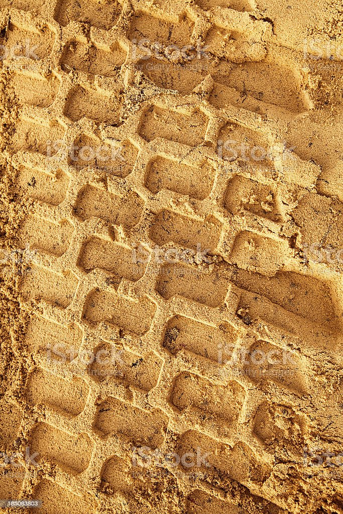 Gold toned trace of a tyre in the sand royalty-free stock photo