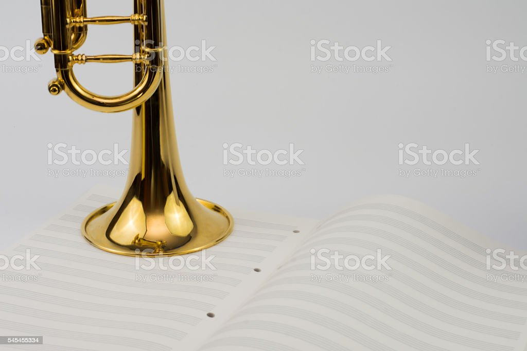 Gold trumpet & blank music sheet stock photo
