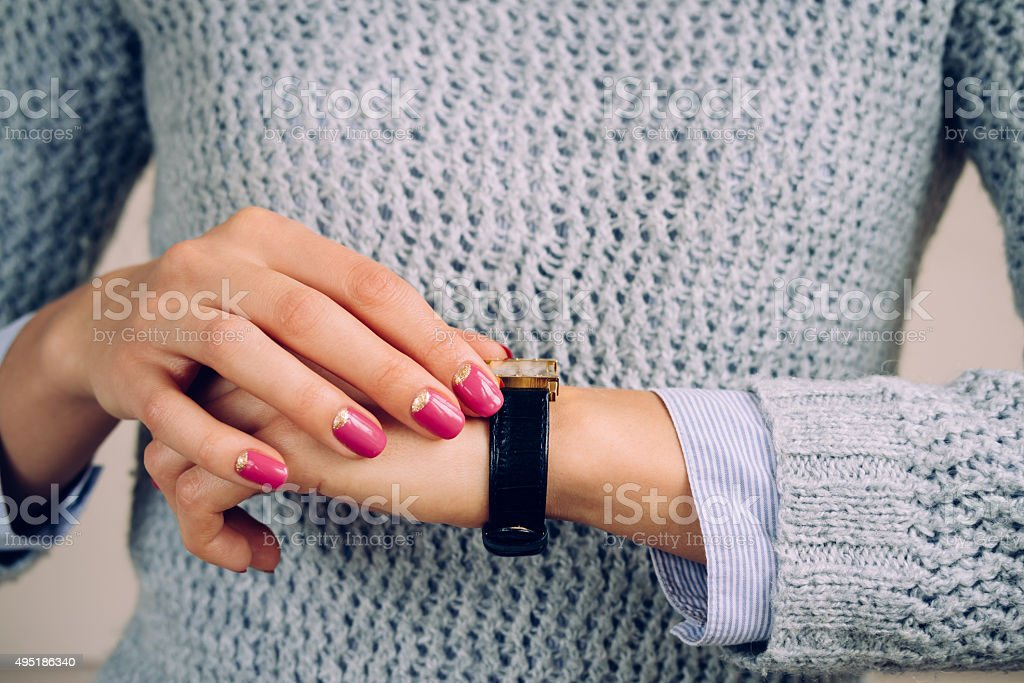 Gold watch with a leather strap on a female hand stock photo