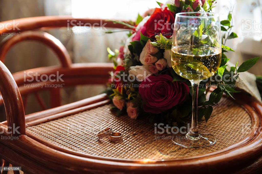 gold wedding rings, a glass of champagne, bouquet on the stock photo