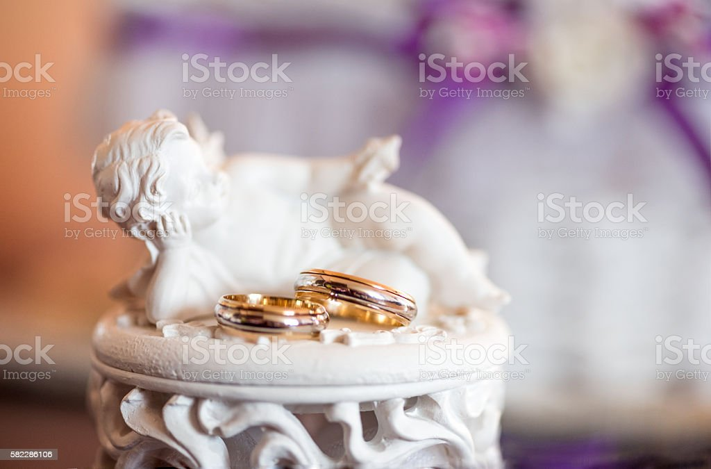 Gold wedding rings on a marble/ceramic Cupid statue stock photo