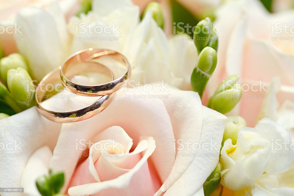 Gold wedding rings on bouquet of flowers for the bride stock photo