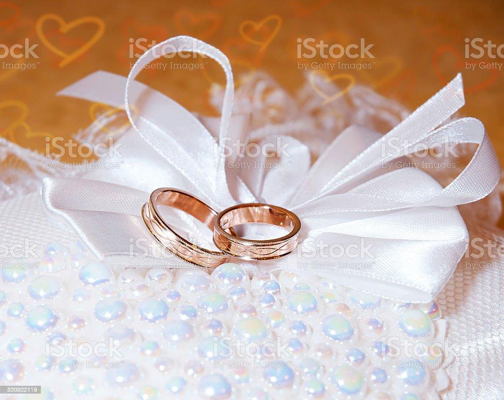 Gold Anneaux de mariage sur le pincushion.  Fond avec coeur photo libre de droits