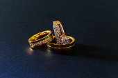 gold wedding rings with diamonds isolated black background