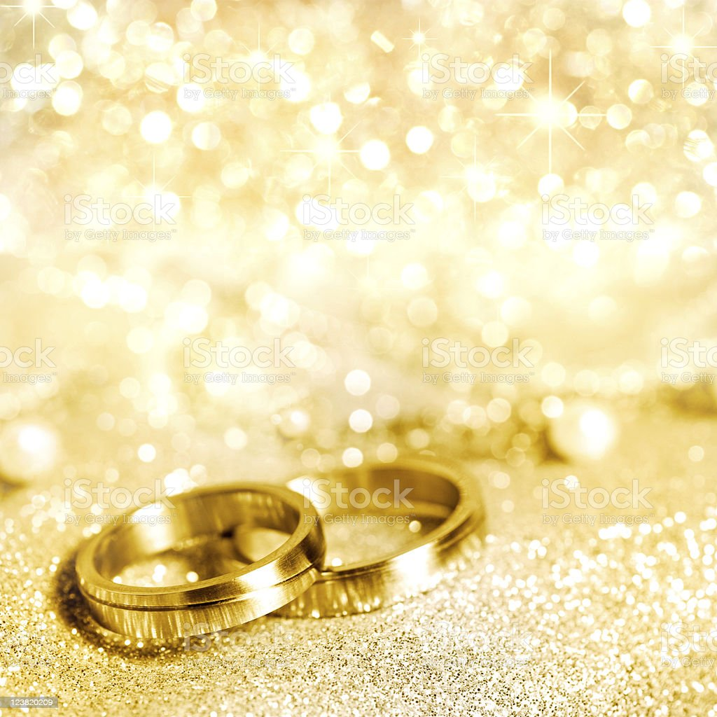 Gold wedding rings with glittering gold background stock photo