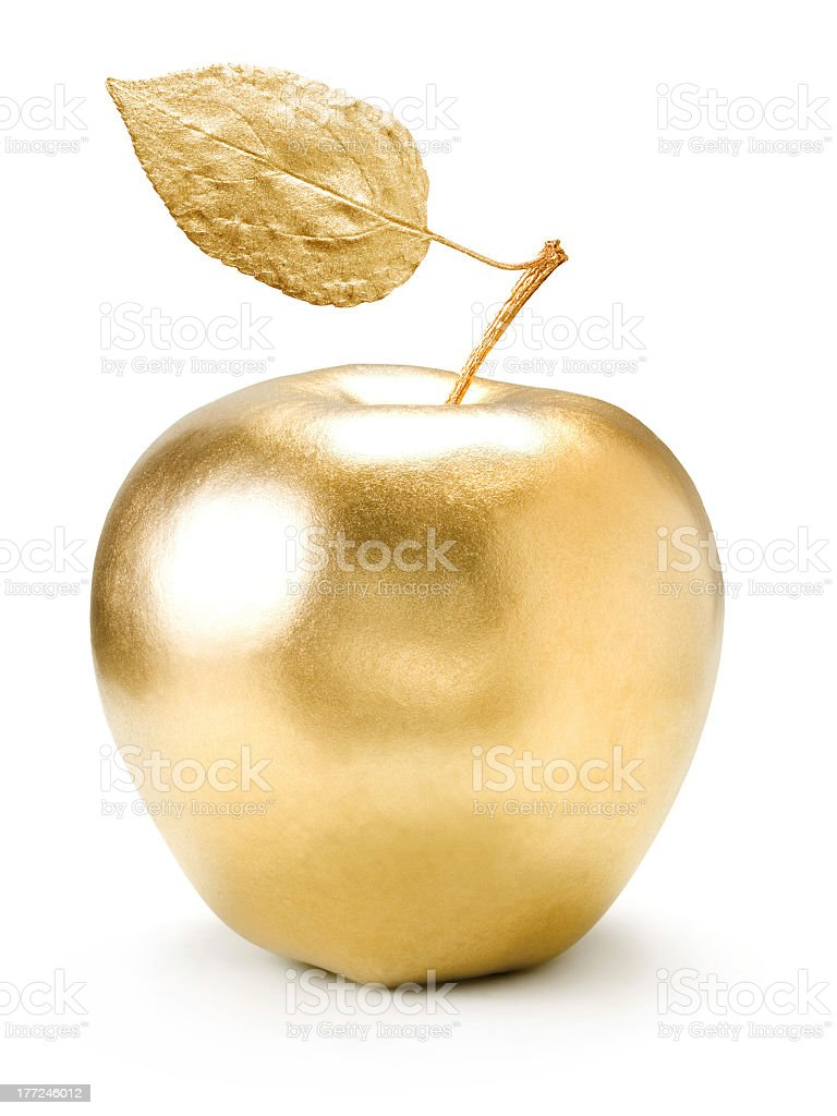 A golden apple with a leaf on a white background stock photo