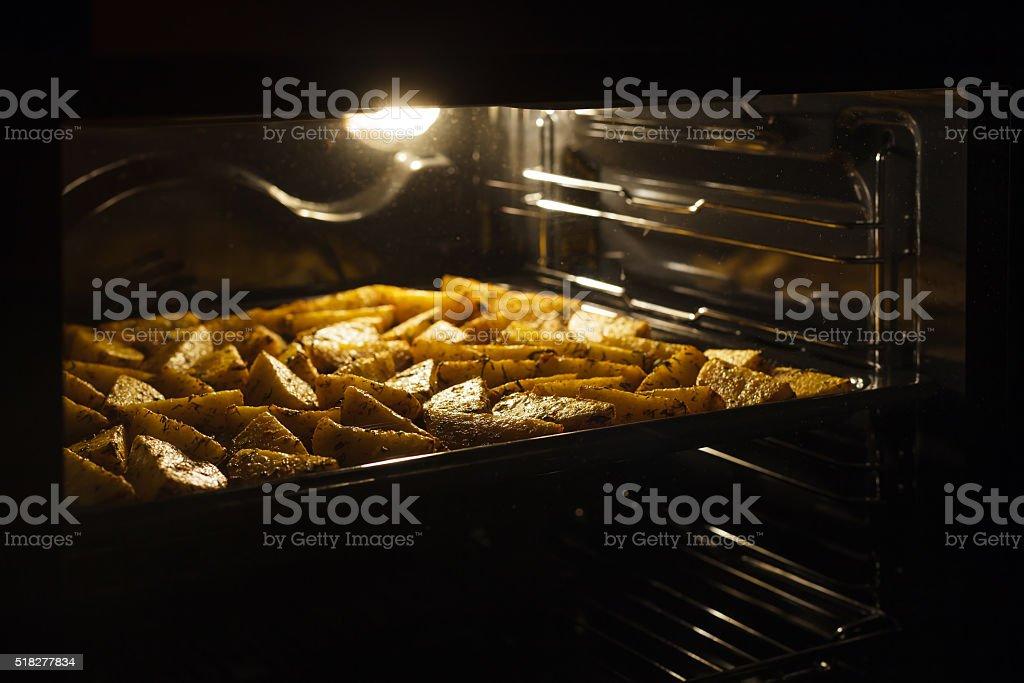 golden baked potato in oven stock photo