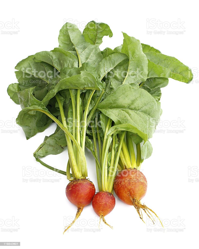 Golden beets with leaves and stem on a white surface stock photo