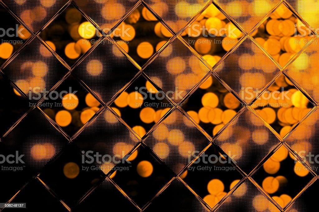 Golden bokeh on black behind glass stock photo