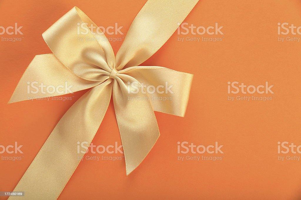 Golden bow on orange background royalty-free stock photo