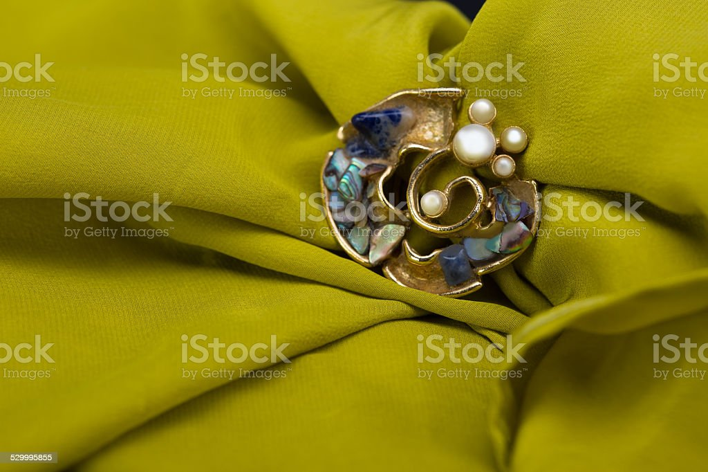 golden brooch on green scarf stock photo