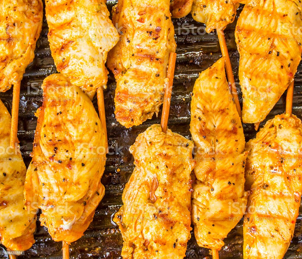 Golden brown chicken pieces on stick in a frying pan stock photo