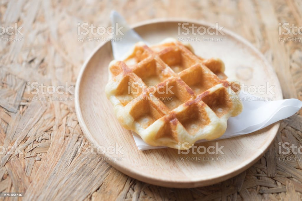 Golden brown waffle on wooden plate stock photo