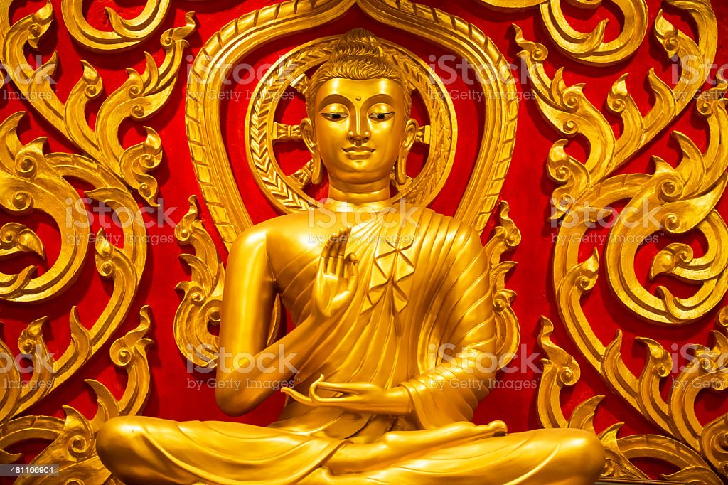 Golden Buddha sits in the temple stock photo