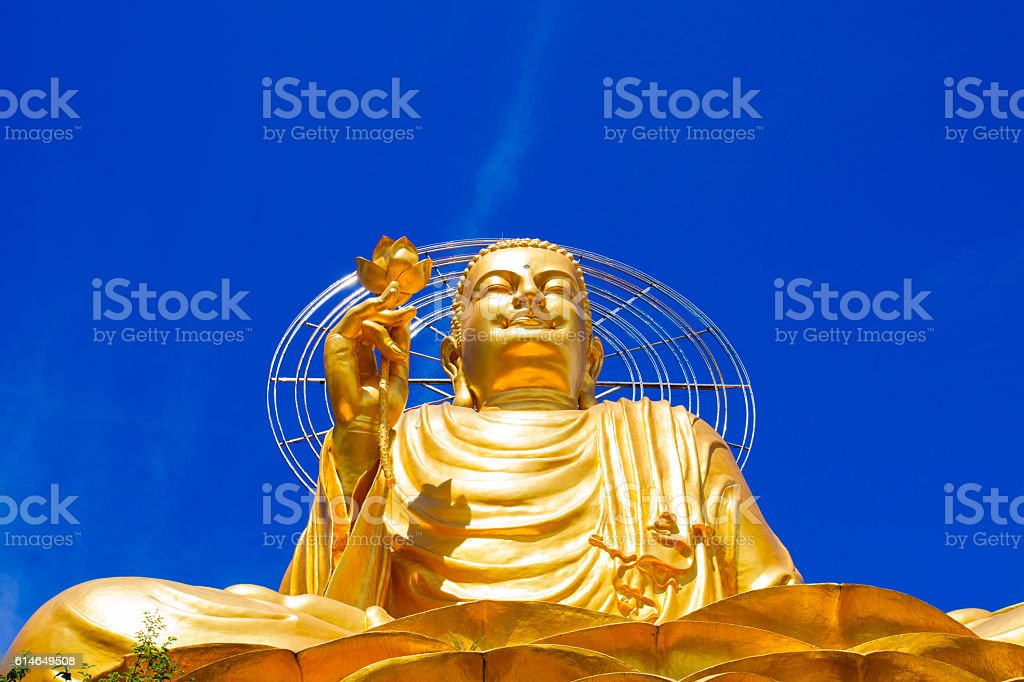 Golden Buddha statue against the clear blue sky stock photo