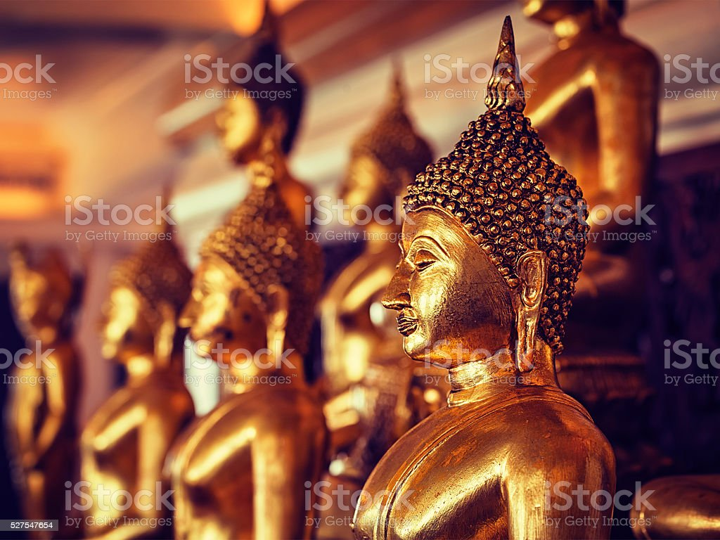 Golden Buddha statues in buddhist temple stock photo