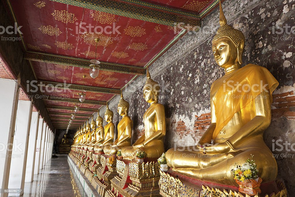 golden buddhas lined up along the wall in temple royalty-free stock photo
