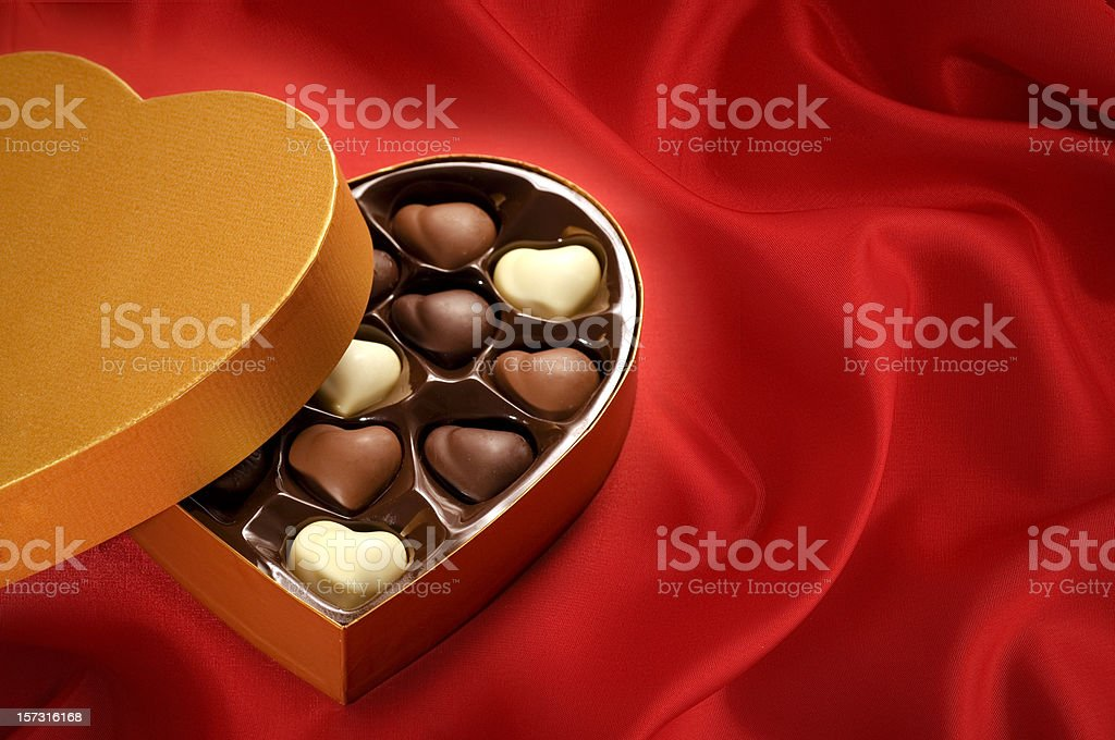 Golden chocolates box on red satin background stock photo