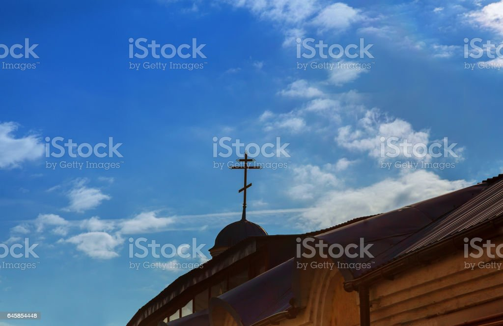 Golden Christian Cross on a dome of an Eastern Orthodox Church with a cloudy blue sky in the background stock photo