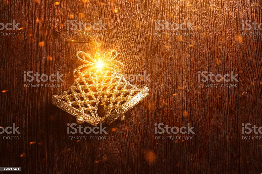 Golden Christmas bells on a dark wooden background stock photo