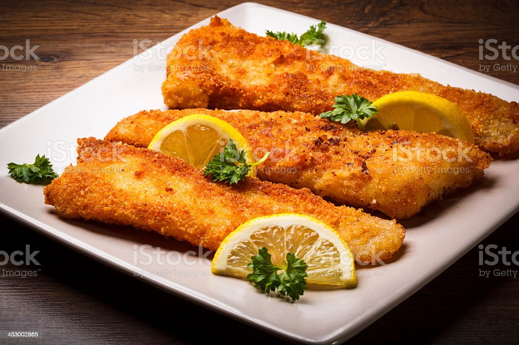 Golden cod filets, garnished with lemon slices stock photo