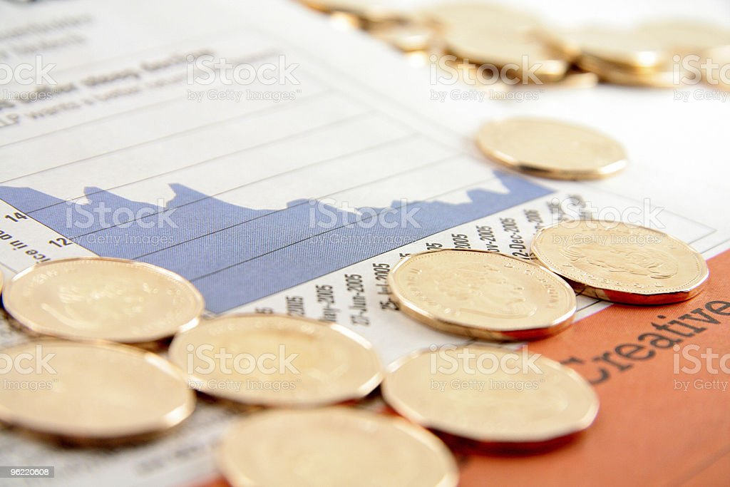 golden coin on the financial pages of a newspaper. stock photo