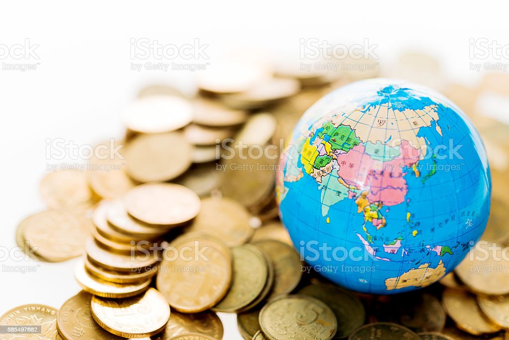 Golden coins and globe stock photo