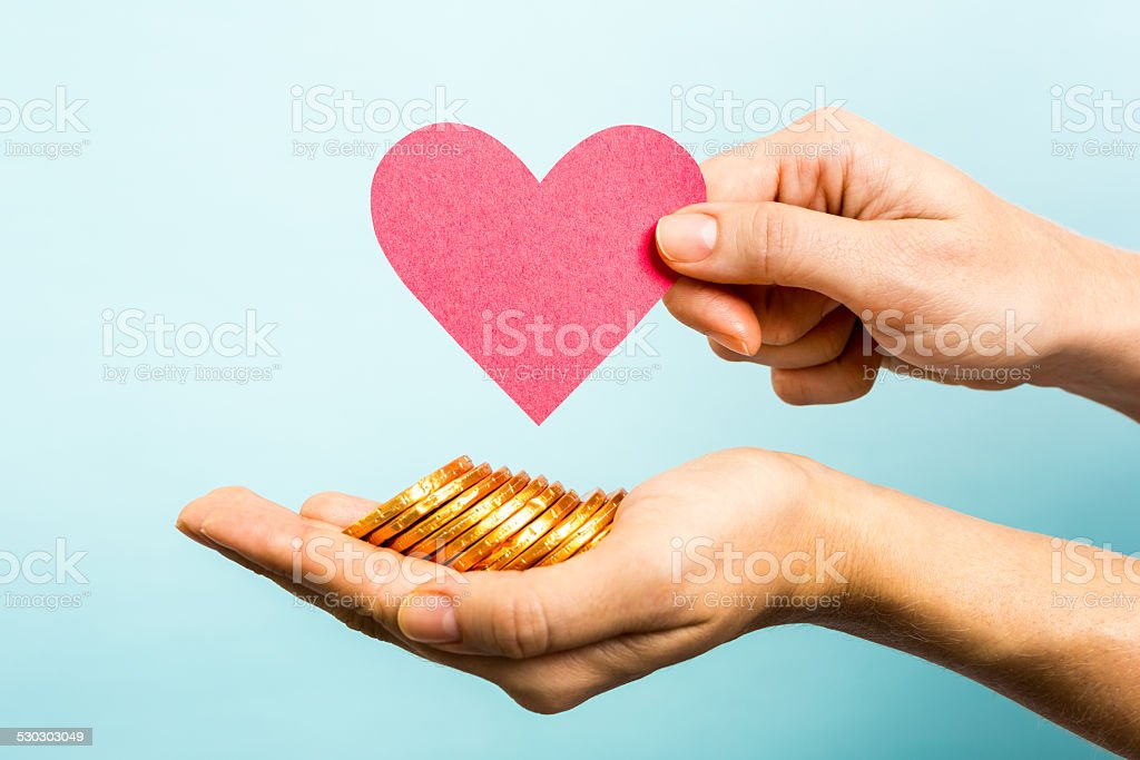Golden coins, red heart paper shape. Love and money concept stock photo