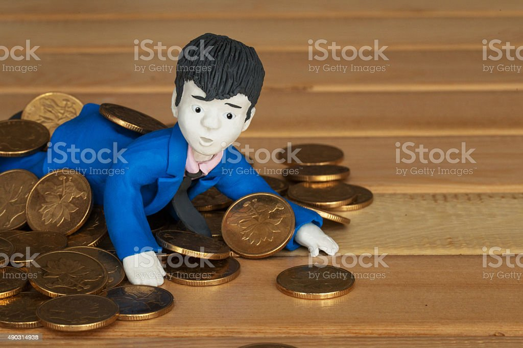 golden coins scattered on a handmade clay office man stock photo