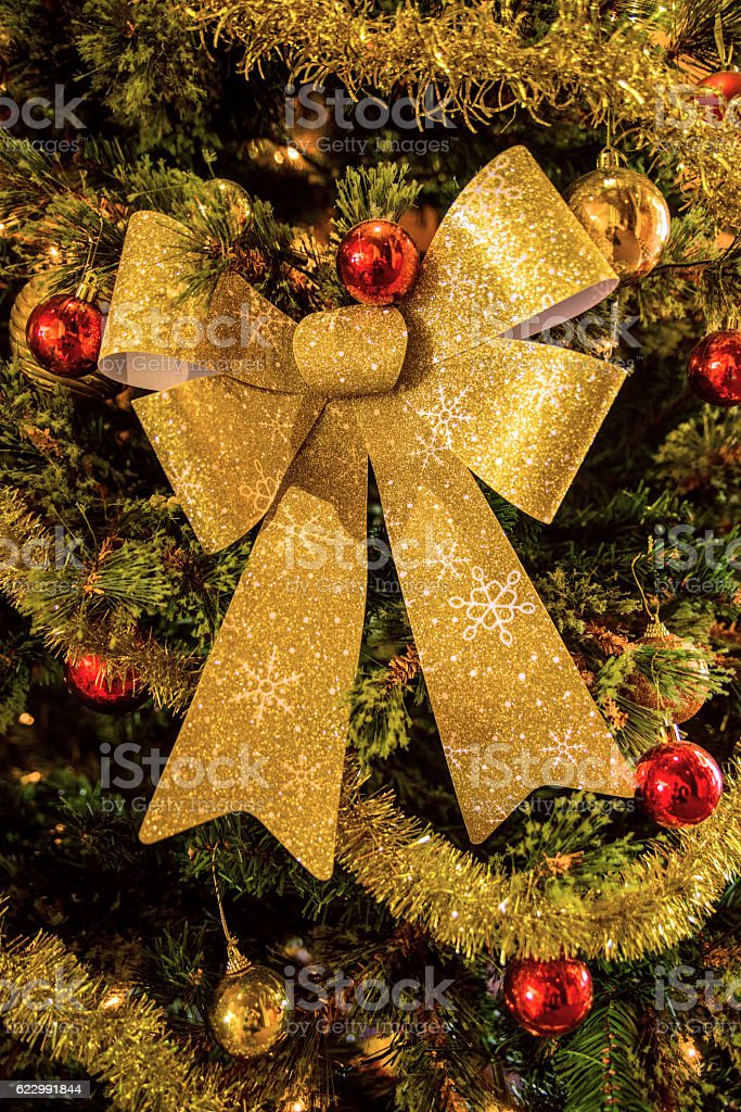 golden colored Christmas decoration on the new year tree stock photo