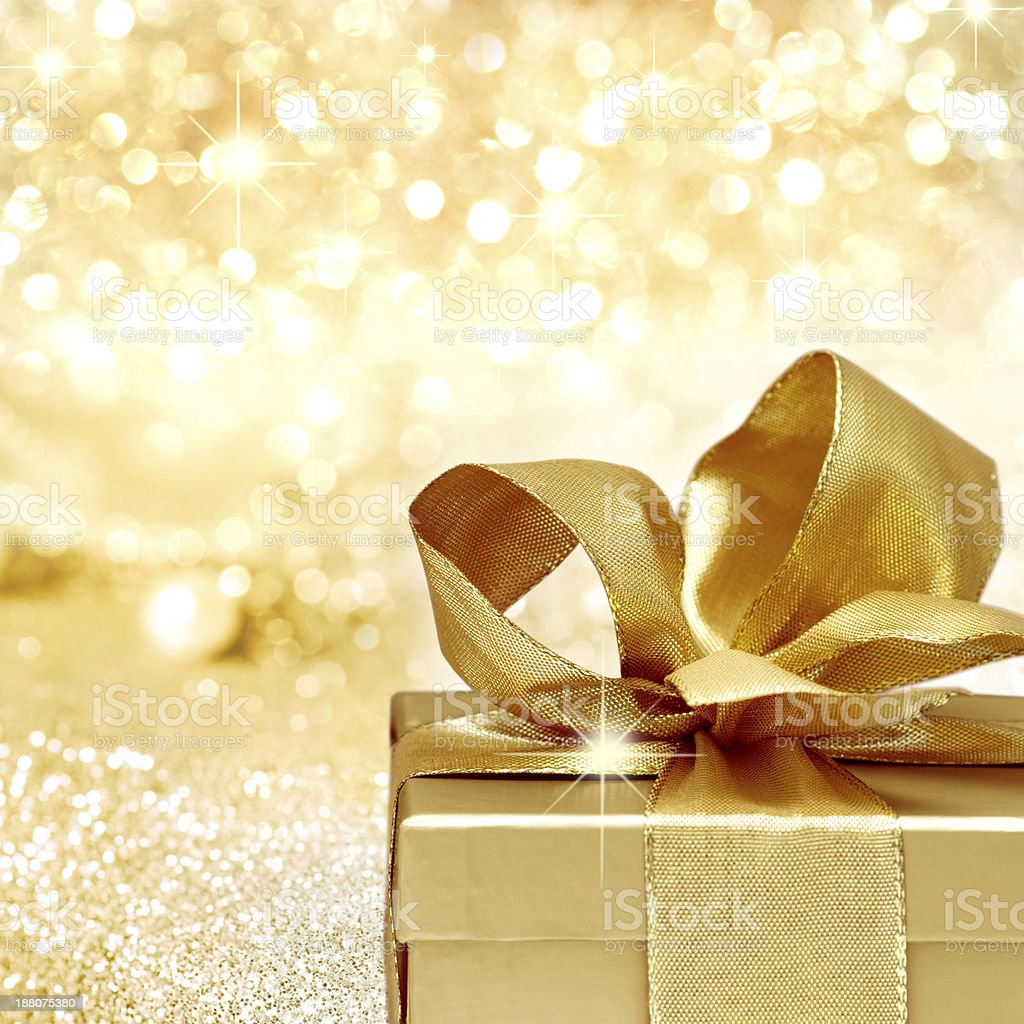 A golden colored Christmas gift on a golden background  stock photo