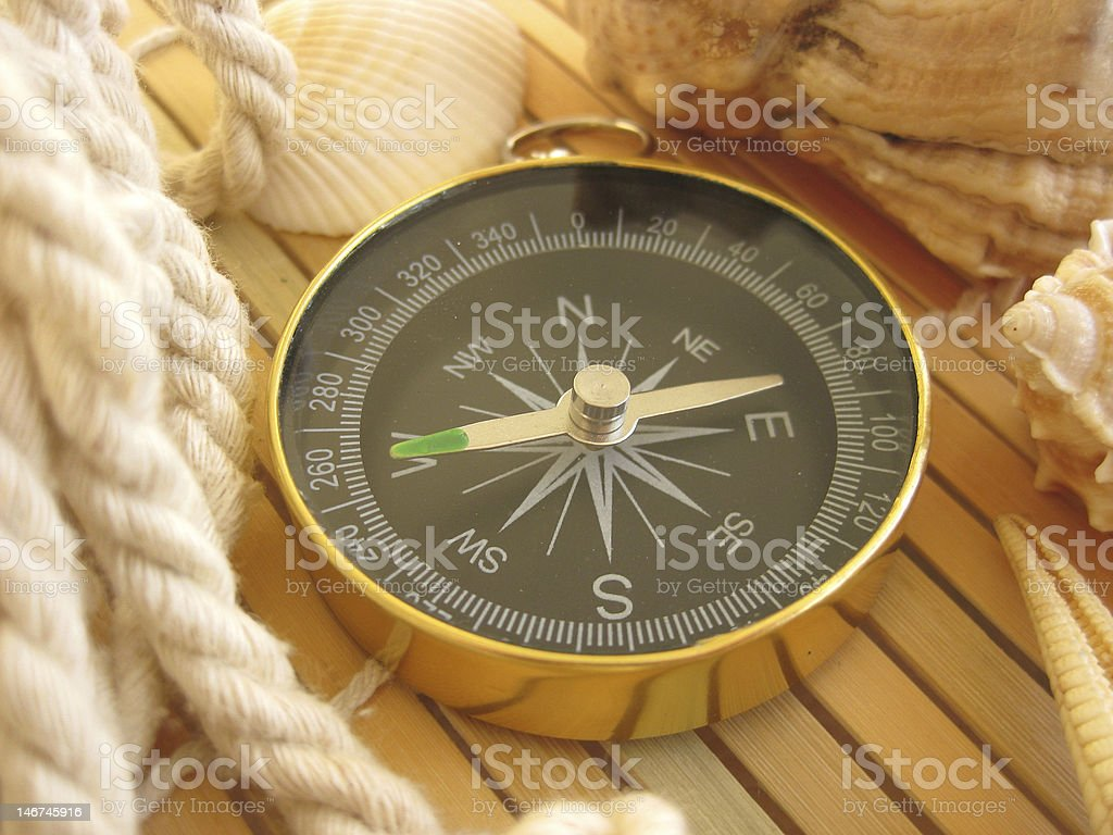 Golden compass on wooden surface stock photo