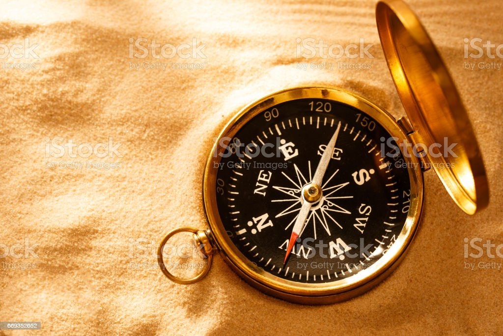 Golden compass with beach sand stock photo