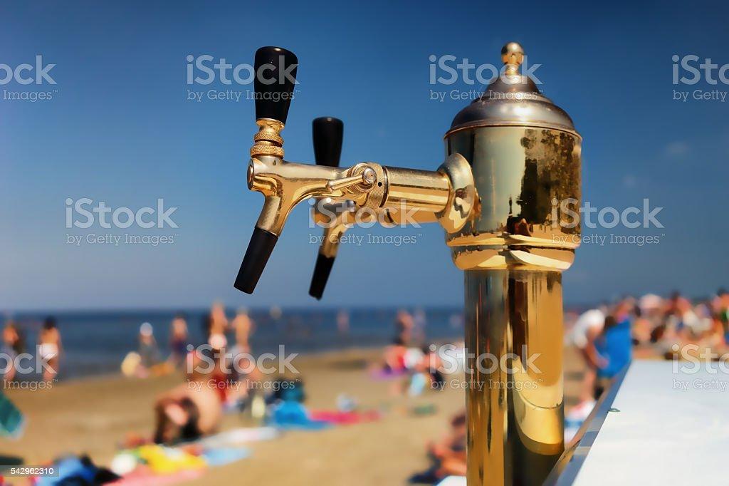 Golden Cranes for bottling beer on a summer beach stock photo