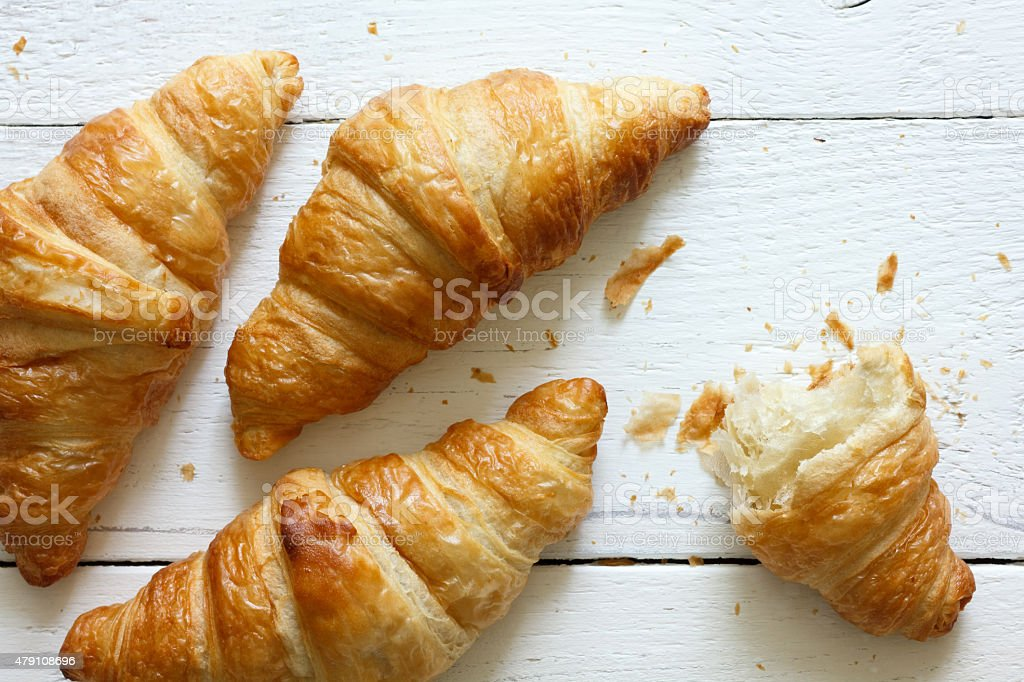 Golden croissants on rustic white wood, from above. stock photo