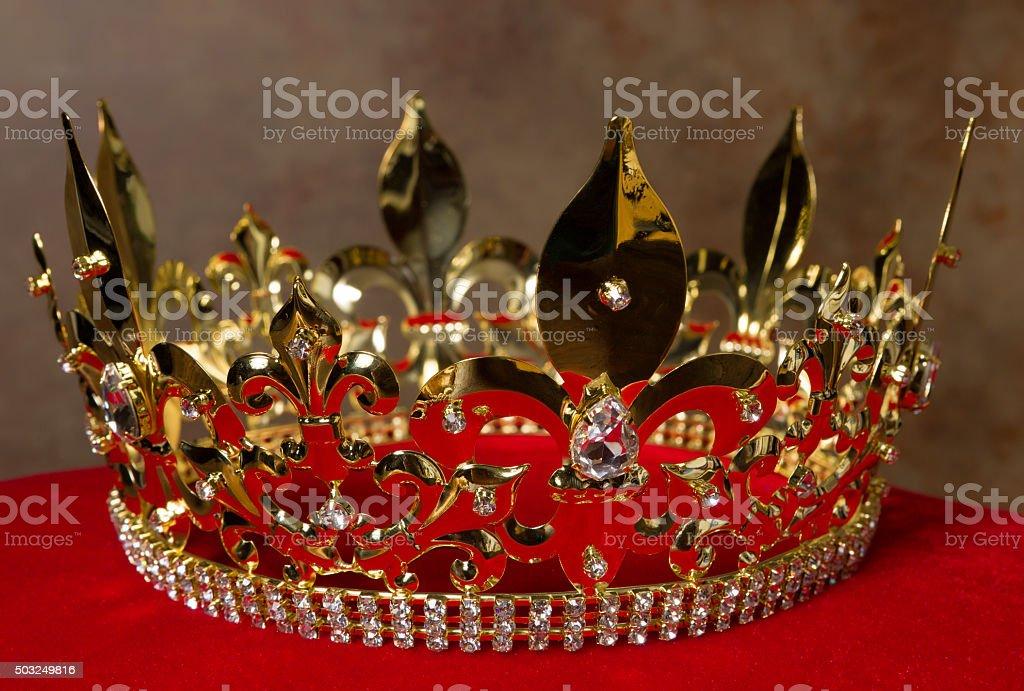 Golden crown on red velvet stock photo