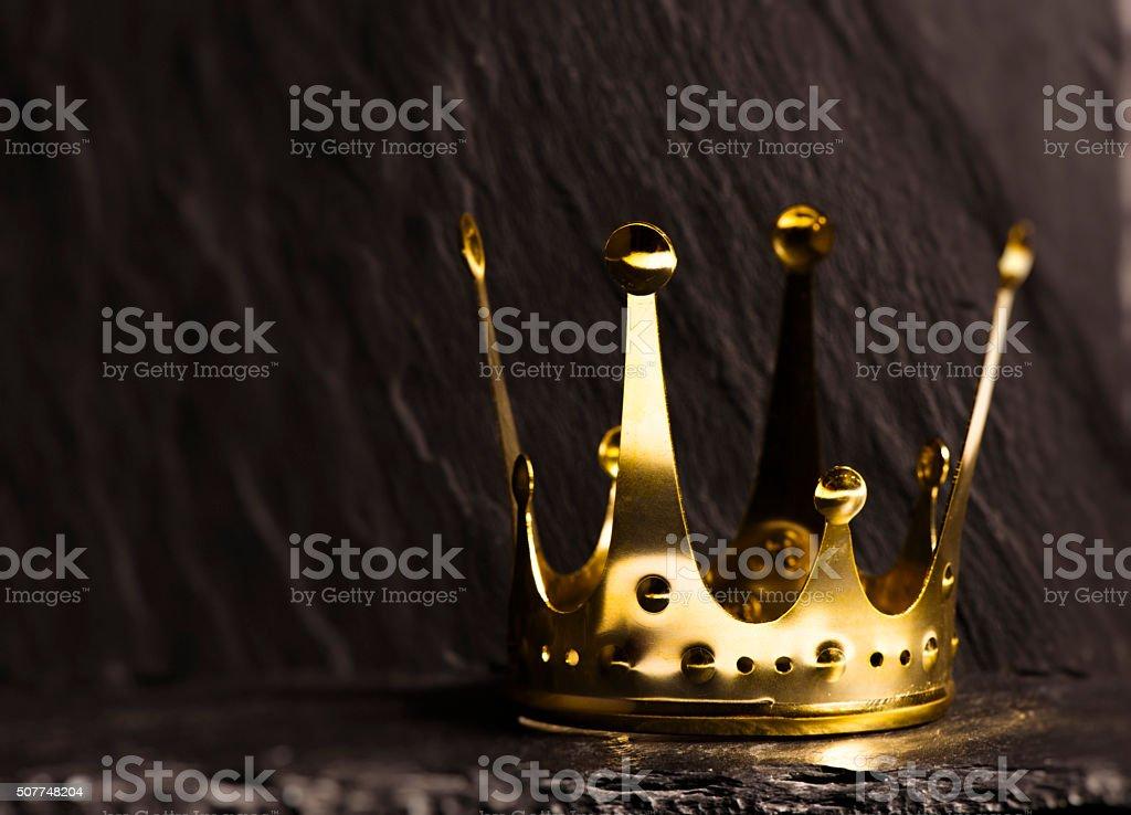 Golden crown with dark background stock photo